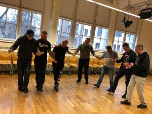 Eine Tanzgruppe, die sich an den Händen hält.